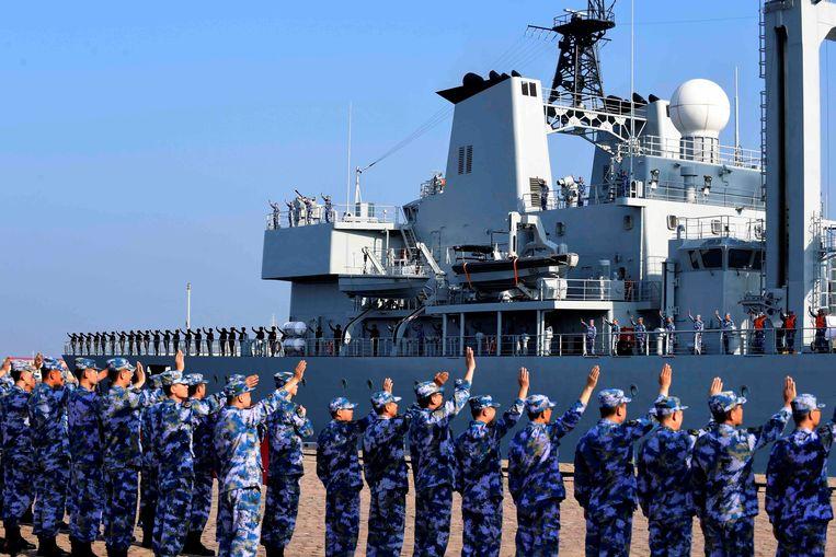 Chinese militairen zwaaien collega's van de marine uit in de haven van Qingdao. Beeld Reuters