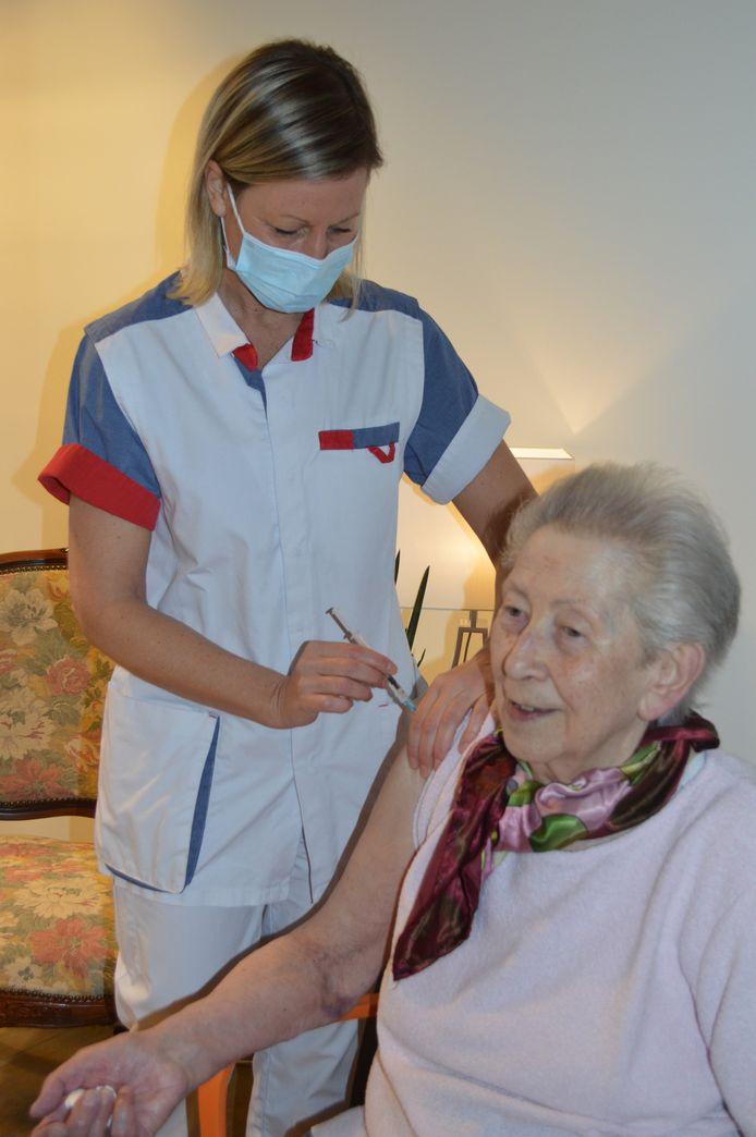 """Juliana Lybaert, bewoner van rusthuis Mariatroon, krijgt haar vaccin toegediend door verpleegkundige  An Daman. """"Hier hebben we reikhalzend naar uitgekeken."""""""