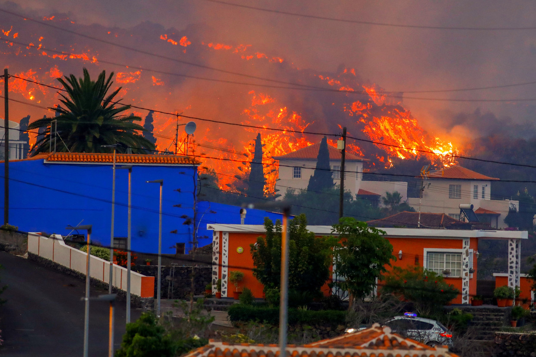 De lava op La Palma nadert maandag een rij huizen bij Los Llanos de Aridane. Volgens vulkaan-expert Rob Govers kan de uitbarsting, die niet heel explosief is, een flinke tijd aanhouden.   Beeld REUTERS