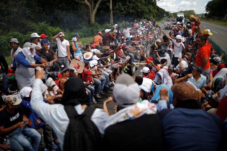 Migranten uit Centraal-Amerika liften nabij de Mexicaanse stad Tapachula mee op een truck richting VS. Beeld REUTERS