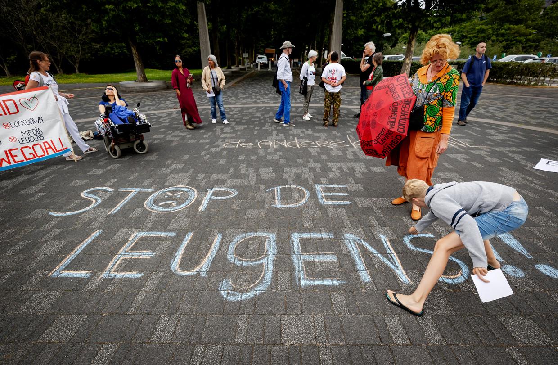 Actievoerders van Viruswaanzin tijdens een stilteprotest bij de NOS op het Mediapark. Bij verschillende mediabedrijven protesteren zij tegen de verslaggeving over het coronavirus.