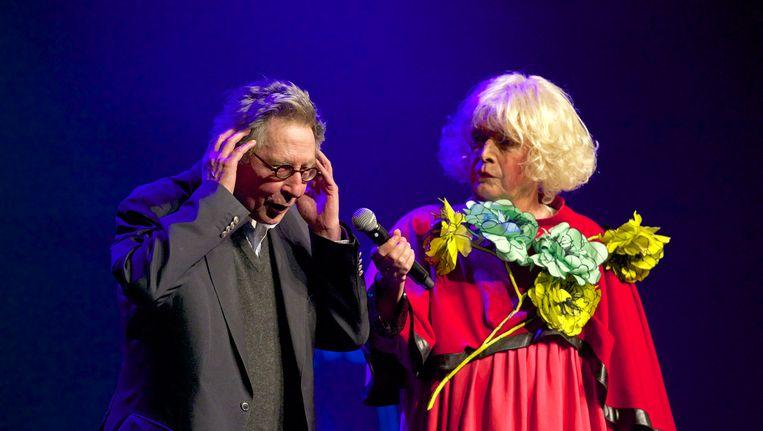 Presentator Margreet Dolman probeert schrijver Maarten Biesheuvel van het podium te loodsen. Beeld Klaas Kloppe