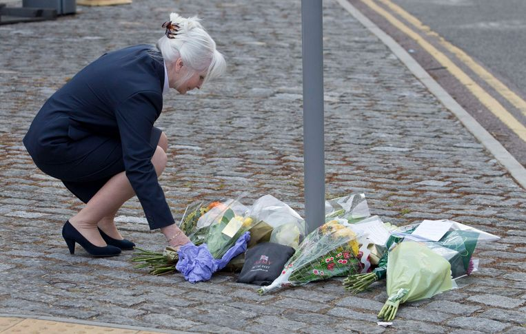Een vrouw legt bloemen neer op de plek waar de Britse militair is afgeslacht. Beeld Reuters