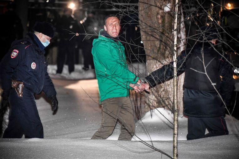 Oppositieleider Aleksej Navalny wordt zondag na terugkeer in Moskou meteen gearresteerd en door agenten meegenomen naar het politiebureau.  Beeld AFP