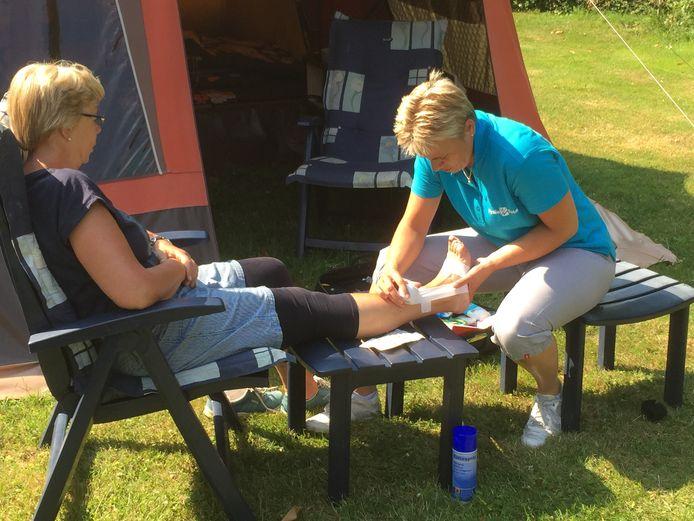 Fysiotherapeute Carla Mastenbroek behandelt een patiënt op de camping.