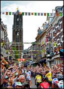 2015. Vertrek van de Tour vanuit Utrecht. Peloton rijdt door de Zadelstraat nabij de Dom