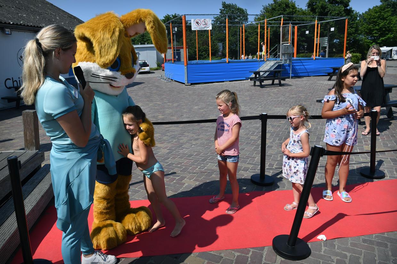 Kinderen staan donderdag in de rij voor een knuffel van Koos Konijn, de mascotte van Roompot, op het Roompot Beach Resort in Kamperland. Beeld Marcel van den Bergh / de Volkskrant