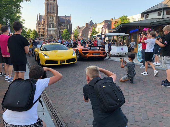 Raf en Lars gaan door de knieën om de Ferrari en Porsche zo goed mogelijk op de foto te zetten.