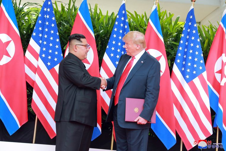 Donald Trump en Kim Jong-un schudden elkaar de hand na ondertekening van het akkoord. Beeld EPA