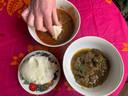 De pindasoep eet je samen met een bol fufu, die je in stukjes in de soep doopt.