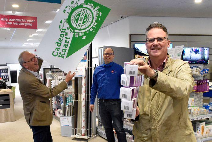 Een klant van Electroworld is blij met de vijf ledlampen, die hij heeft gekocht met de cadeaukaart. Links Chris de Groot van de Stichting Duurzaam Woerden. In het midden eigenaar Vincent de Groot van Electroworld.