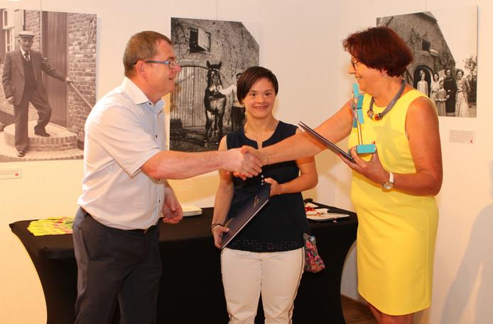 Wethouder Hans van de Looij en Lisa Loosman overhandigen de Ster en oorkonde aan een van de vrijwilligers van museum 't Oude Slot in Veldhoven.