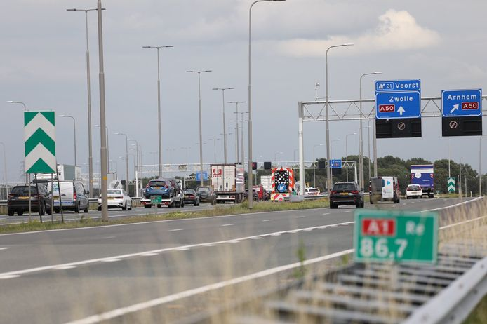 Wachtende automobilisten. Een brandende auto veroorzaakte een file op de A1 bij Apeldoorn.