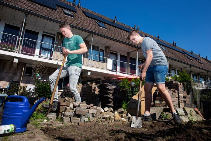 Gerjan van Eck (links) en Lennart Meeuse van het Van Lodenstein College uit Kesteren (beiden 16) steken de handen uit de mouwen in een tuin in Veenendaal.