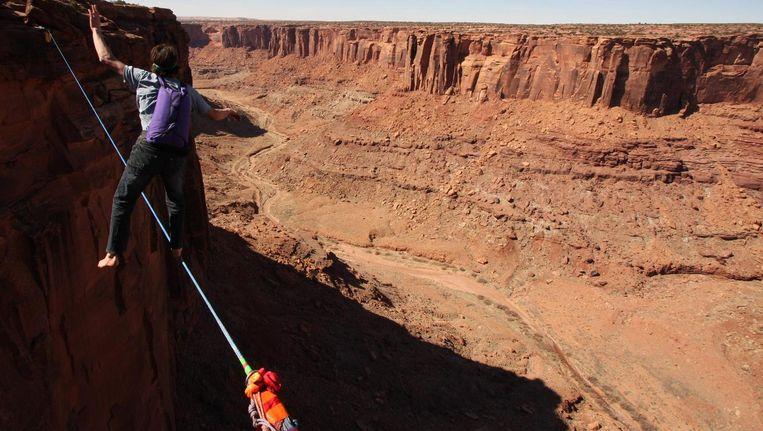 Dean Potter hield zich niet enkel met klimmen en basejumpen bezig, maar was ook bedreven in 'high lining'. Dat is balanceren op een stalen koord op grote hoogte. Hij deed dat vaak zonder beveiliging, maar wel met een parachute om om vervolgens te basejumpen. Beeld PHOTO_NEWS