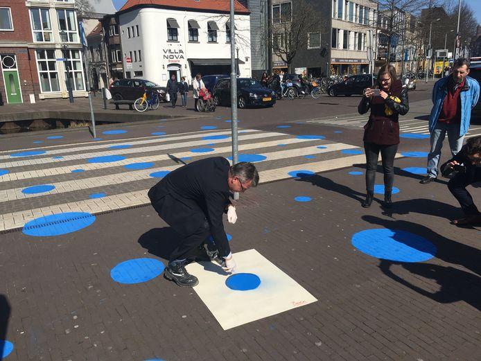 Wethouder Alfred Arbouw brengt een blauwe stip aan op de Markendaalseweg op de plaats waar de Nieuwe Mark straks gaat lopen.