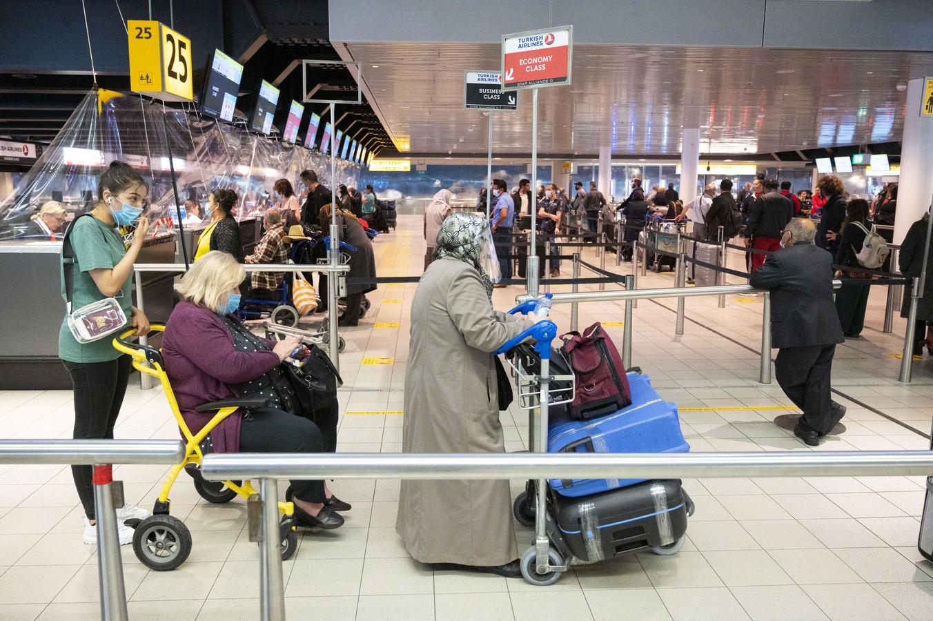 Foto ter illustratie. Reizigers bij een incheckbalie van Schiphol.