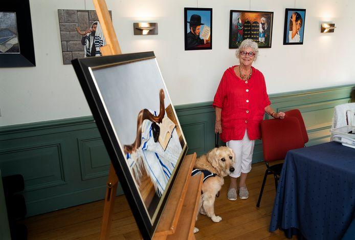 Suzanna van Duffelen met hulphond Kiki bij enkele van haar joodse schilderijen.