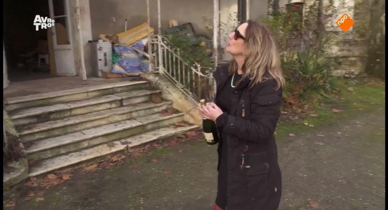 Emmy, met champagne, voor haar zojuist gekochte kasteel. Beeld Avrotros