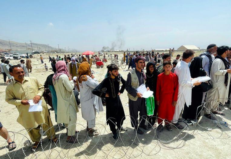 Afghanen wachten op evacuatie bij de luchthaven van Kaboel. Beeld AP