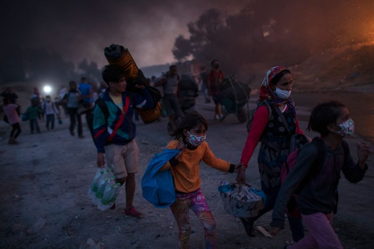 Vluchtelingen op de vlucht voor de vlammen in het kamp Moria op het eiland Lesbos. Beeld AP