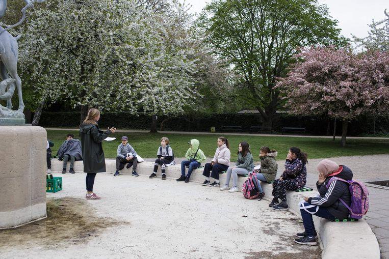 Een lerares spreekt haar leerlingen van de Norrebro Park basisschool in Kopenhagen. In Denemarken gingen de basisscholen op 15 april alweer open, met als voorwaarde dat de lessen zoveel mogelijk buiten moesten worden gegeven.  Beeld AFP