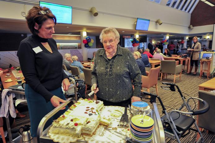 Mevrouw Dekkers (89) mag de taart aansnijden nadat de koopovereenkomst is getekend.