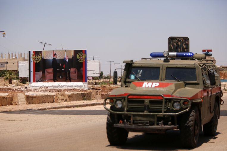 Een Russisch militair voertuig rijdt langs een poster waarop de Syrische president Basahr al Assad de hand van de Russische president Poetin schudt. Volgens het Syrisch Observatorium voor de Mensenrechten kwamen gisteren bij Russische bombardementen minstens drie vrouwen en twee kinderen om. Beeld REUTERS