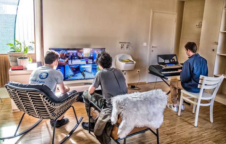 Twee jongens zijn aan het gamen, een derde speelt keyboard. Beeld Tim Dirven