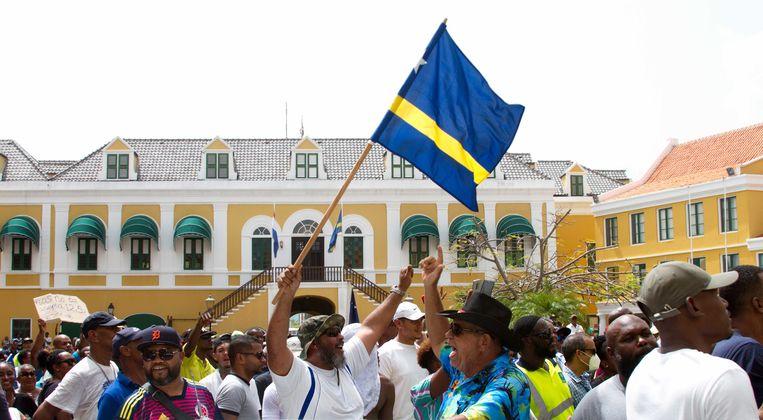 Deelnemers tijdens een manifestatie voor het regeringsgebouw. De betogers eisen het aftreden van minister-president Eugene Rhuggenaath. Beeld ANP