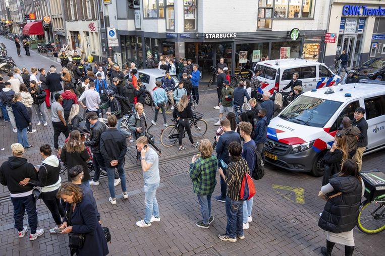 Politie en publiek bij de Lange Leidsedwarsstraat in Amsterdam. Bij een schietpartij is misdaadverslaggever Peter R. de Vries zwaargewond geraakt.  Beeld ANP