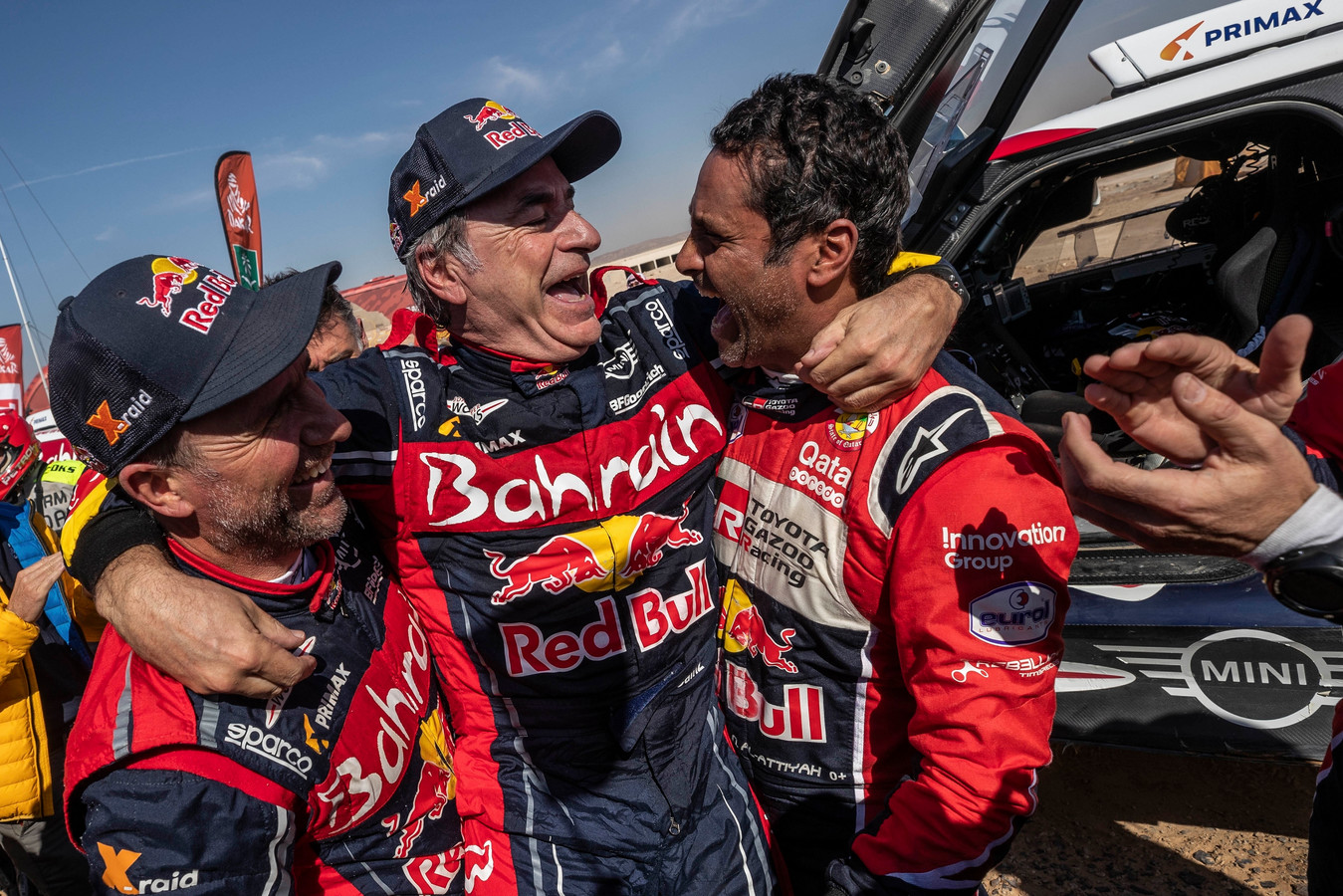 Carlos Sainz (midden) wordt gefeliciteerd door Stephane Peterhansel (links) en Nasser Al-Attiyah (rechts).