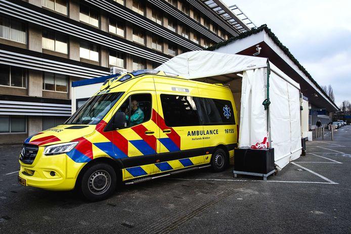 Een ambulance bij een portakabin bij de spoedeisende hulp van het Groene Hart Ziekenhuis, waarin corona(verdachte) patienten worden opgevangen