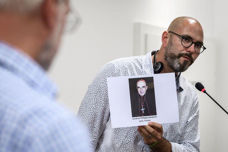 François Devaux, slachtoffer van seksueel misbruik door priester Preynat, laat tijdens een persconferentie een foto van kardinaal Barbarin zien. Die hoge geestelijke is veroordeeld omdat hij wist van het misbruik maar niet ingreep. Beeld AFP
