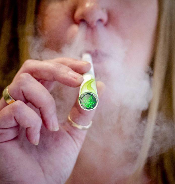 Een vrouw rookt een elektronische sigaret met cannabissmaak.