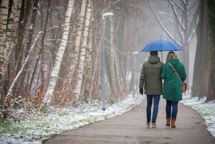 Met de paraplu door de sneeuw omdat er alweer regent valt en dooit.