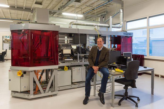 Marc Evers bij een industriële printer die wordt ontwikkeld voor een nieuw soort kunststof gebitsbeugeltjes.