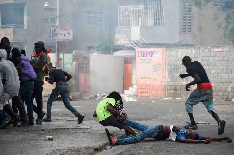 Een man valt terwijl hij het lichaam van een dode kameraad mee wil slepen tijdens protesten in de Haitiaanse hoofdstad. Beeld AFP