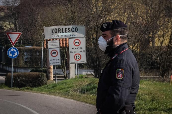 Een agent in Italië draagt een mondkapje ter bescherming bij een controlepunt