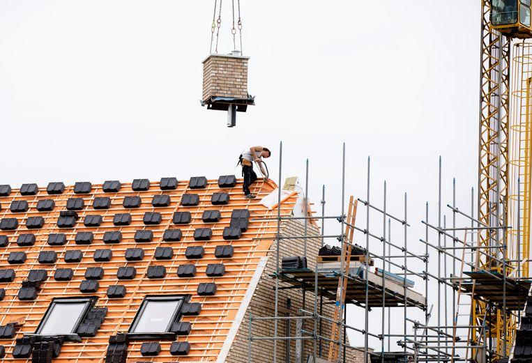 Een bouwvakker aan het werk op het dak van een nieuwbouwwoning.  Beeld BART MAAT