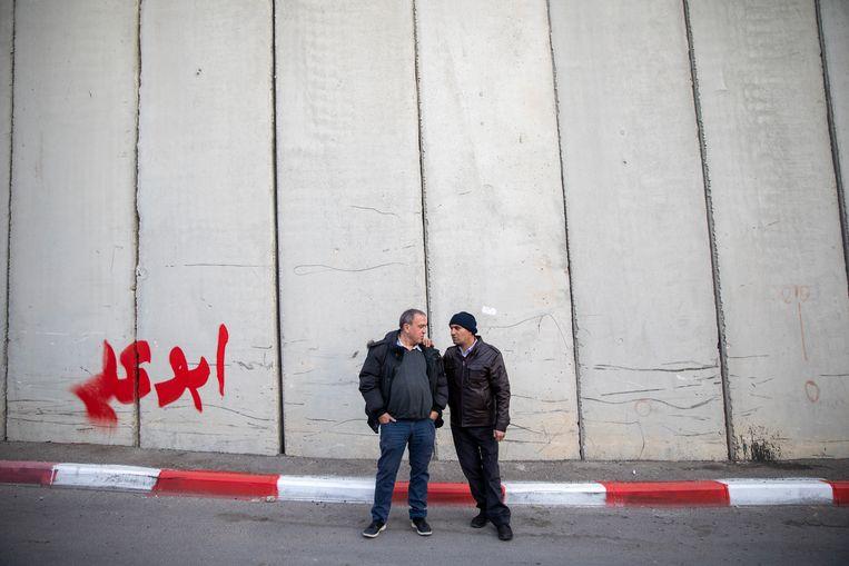 Rami Elhanan en Bassam Aramin bij de muur die Israël en de Palestijnse gebieden scheidt. 'In onze hoofden zijn muren ontstaan die sterker zijn dan die van beton.' Beeld Oded Balilty / AP