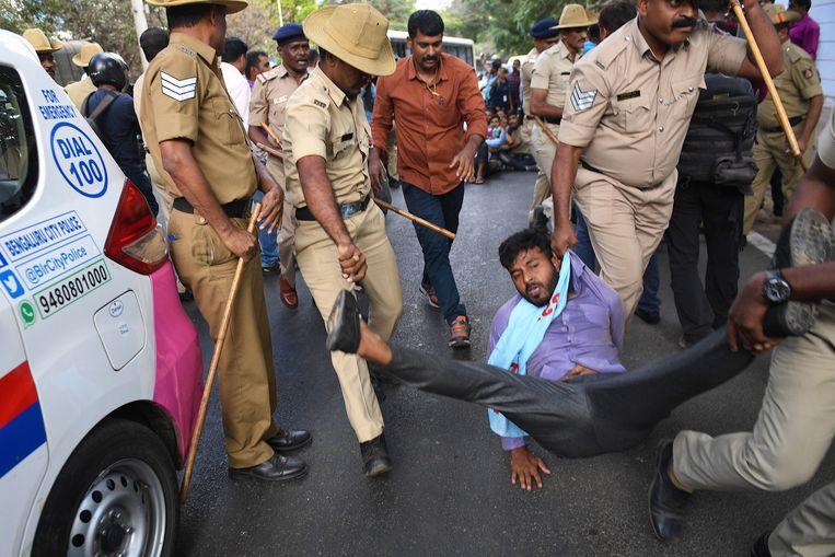 Politieagenten pakken een jonge betoger op in Bangalore.  Beeld AFP