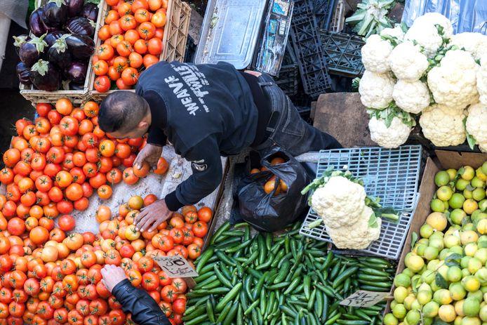 Archiefbeeld. Een Palestijn verkoopt verse groenten en fruit op een markt in Ramallah.