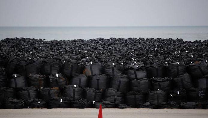 Zwarte 1000 liter-zakken met besmette grond, bladeren en puin op het strand van Tomioka, in de Fukushima prefectuur.