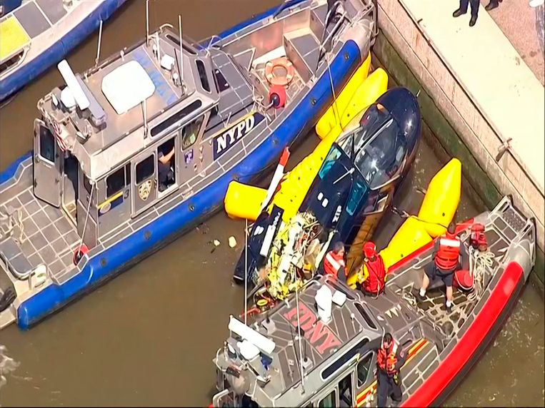 Politie en brandweer proberen de helikopter naar boven te halen.