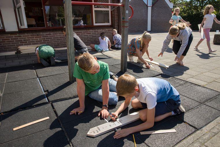 De elfjarige Gert (groen T-shirt) aan de slag met een medeleerling.   Beeld Arie Kievit