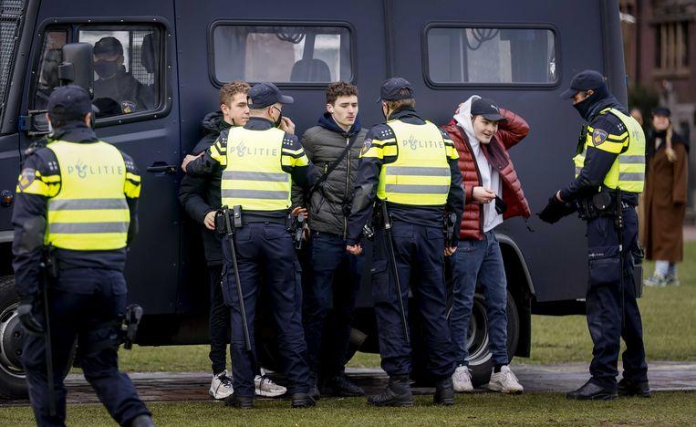 Agenten controleren mensen bij een protest op het Museumplein. De politie mag binnenkort bij wijze van proef preventieve fouilleeracties gaan uitvoeren. Beeld ANP