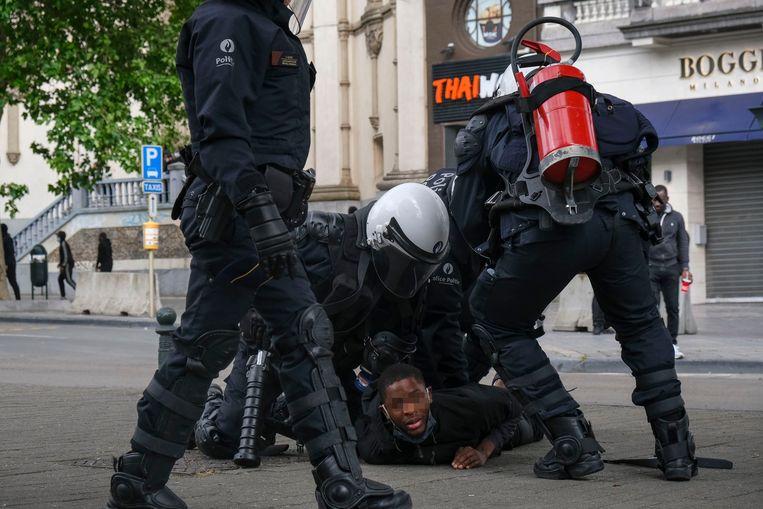 Agenten dwingen een demonstrant tegen de grond tijdens BLM-protesten in Brussel. Beeld BELGA