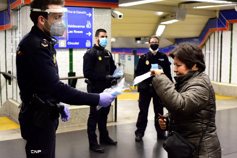 In een Madrileens metrostation deelt de politie mondkapjes uit. Beeld Getty Images