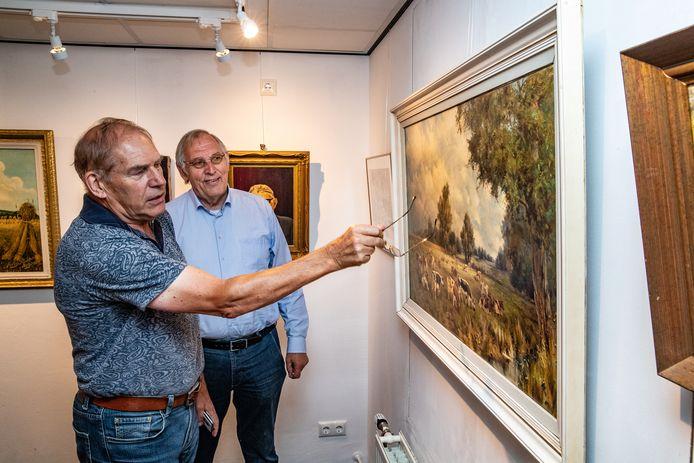 Henk Mulder (l) en Jan Beumer vertellen de verhalen achter de schilderijen van oude Holtense kunstenaars.